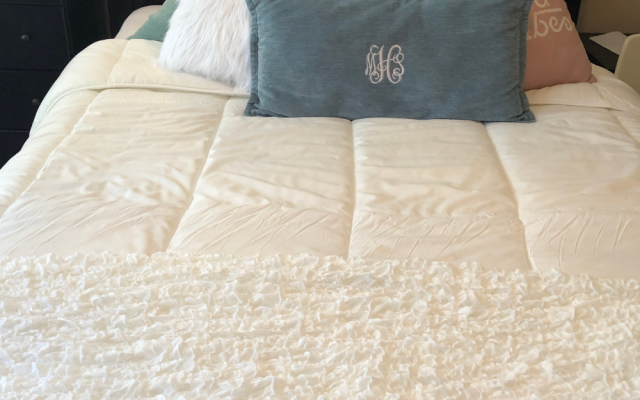 Bedspread and throw from IKEA make a cozy and thrifty first apartment bedroom.